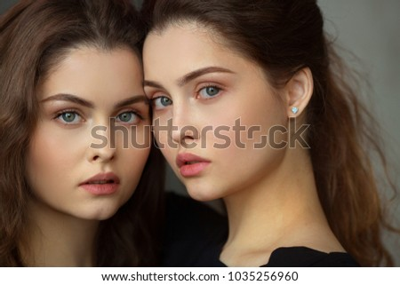 portrait of two beautiful young girls of twin sisters with flowing hair #1035256960