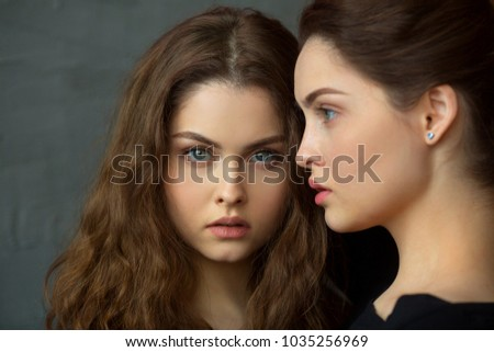portrait of two beautiful young girls of twin sisters with flowing hair #1035256969