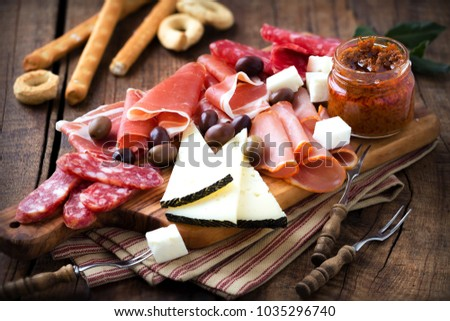 Cured meat and cheese platter of traditional Spanish tapas - chorizo, salsichon, jamon serrano, lomo and slices of goat cheese - served on wooden board with olives and bread sticks #1035296740