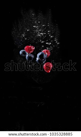 raspberries and huckleberries falling in water.  High speed flash splash photography