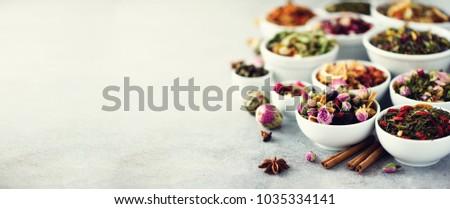 Assortment of dry tea in white bowls. Tea backgound: green, black, floral, herbal, mint, melissa, ginger, apple, rose, lime tree, fruits, orange, hibiscus, raspberry, cornflower, cranberry. Banner. #1035334141