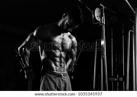 Muscular Man Doing Heavy Weight Exercise For Chest On Machine With Cable In The Gym Royalty-Free Stock Photo #1035345937