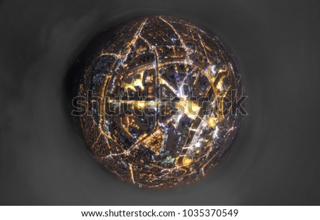 Tiny planet of a city center at night / small earth sphere photo above a city center