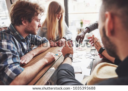 Group of creative multietnic friends sitting at wooden table. People having fun while playing board game. #1035393688