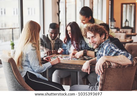 Group of creative friends sitting at wooden table. People having fun while playing board game. #1035393697
