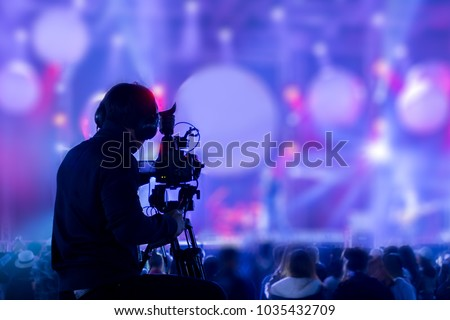 The filmmaker is recording and broadcasting live concerts on camcorders. Professional Video Recording Business Royalty-Free Stock Photo #1035432709