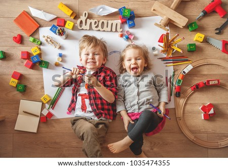 Kids drawing on floor on paper. Preschool boy and girl play on floor with educational toys - blocks, train, railroad, plane. Toys for preschool and kindergarten. Children at home or daycare. Top view #1035474355