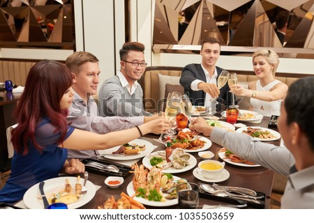 Multiethnic friends clinking with champagne glasses at dinner #1035503659