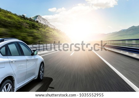 White car rushing along a high-speed highway in the sun. #1035552955