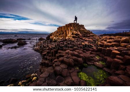 Man standing on top of basalt columns at Giant's Causeway, Ireland Royalty-Free Stock Photo #1035622141