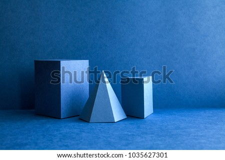 Geometrical figures still life composition. Three-dimensional prism pyramid tetrahedron rectangular cube objects on blue background. Platonic solids figures, simplicity concept photography. #1035627301