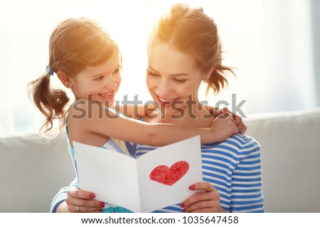 Happy mother's day! Child daughter congratulates moms and gives her a postcard   #1035647458