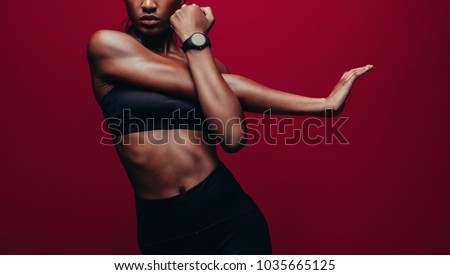 Cropped shot of woman stretching her arms. Female doing warmup stretching workout on red background. #1035665125
