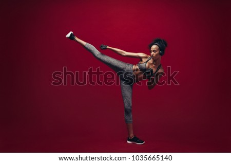 African female fighter practising high kick in studio. Full length shot of fit woman athlete performing a high kick over red background. Martial arts woman exercising taekwondo. Royalty-Free Stock Photo #1035665140