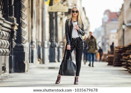 Young pretty girl walk on the street with cup of coffee on her hand and wear sunglasses, sunny day weather Royalty-Free Stock Photo #1035679678