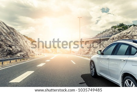White car rushing along a high-speed highway in the sun. #1035749485