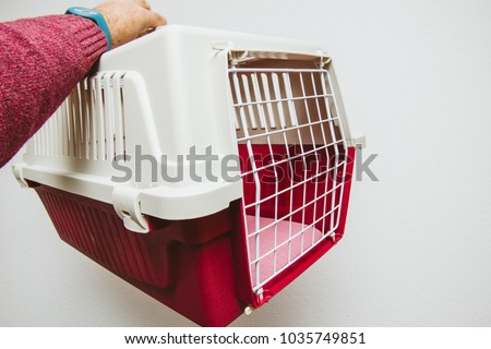 Man hand holding against white background animal pet cage used for cat and dog transportation in planes and buses #1035749851