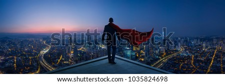 Businessman in suit and cape hero stand at rooftop looking great cityscape view and thinking business plan of the future . Night scene . Royalty-Free Stock Photo #1035824698