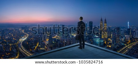Businessman stand at rooftop looking great cityscape view and thinking business plan of the future . Night scene . #1035824716