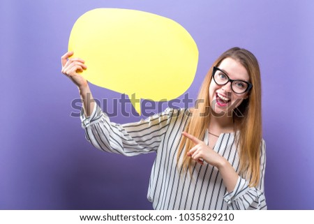 Young woman holding a speech bubble on a purple background #1035829210