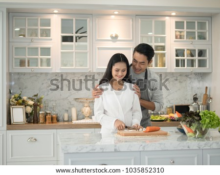 Young asian expecting pregnant couple cooking together in the kitchen at home.  #1035852310