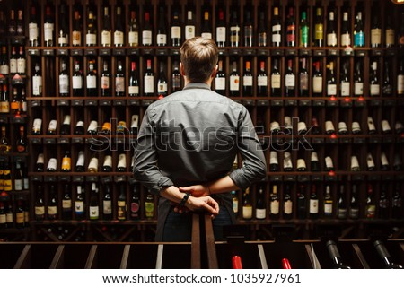Bartender at wine cellar full of bottles with exquisite drinks #1035927961