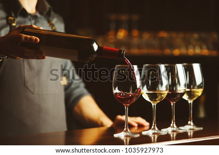 Bartender pours red wine in glasses on wooden bar counter #1035927973