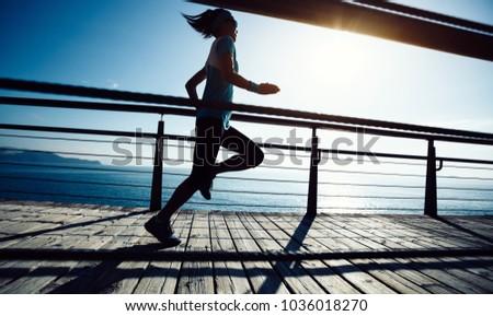 Sporty female runner running on seaside boardwalk during sunrise  #1036018270
