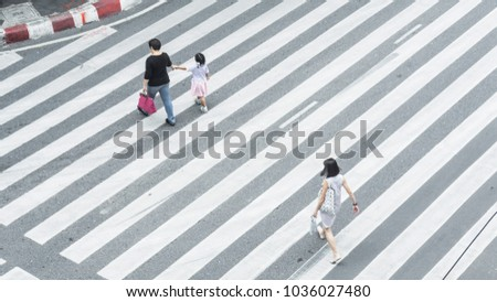 Crowd of people and group of family with child walk on street pedestrian crossroad in the city street ,from top view ,bird eye view. #1036027480