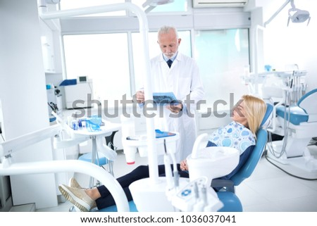 The dentist looks at the X-ray of a patient's tooth in a dentist's office #1036037041