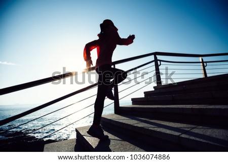 sporty fitness female runner running upstairs on coast trail #1036074886