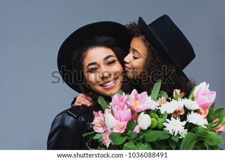 daughter kissing her mother while she holding bouquet isolated on grey
