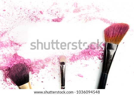 Traces of vibrant pink powder and blush forming a frame, with makeup brushes. A template for a makeup artist's business card or flyer design, with a place for text
