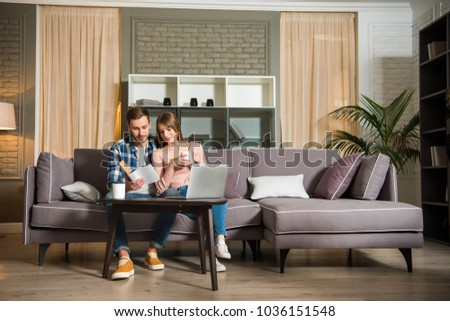 Couple reading book in living room with laptop on table in cozy living room #1036151548