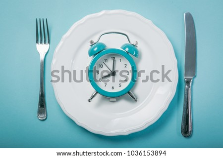 Intermittent fastin concept - empty plate on blue background Royalty-Free Stock Photo #1036153894