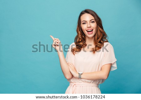 Image of happy young lady standing isolated over blue background. Looking camera pointing.