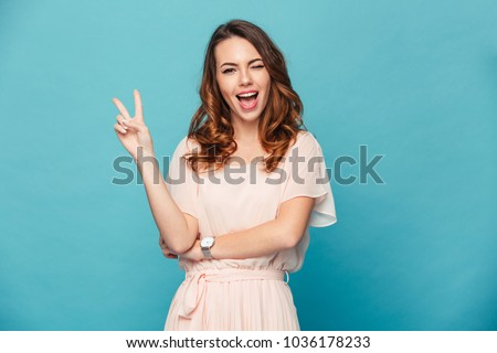 Image of cute young lady standing isolated over blue background. Looking camera showing peace gesture. #1036178233