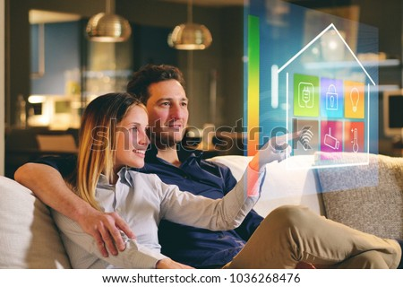 A couple sitting on the sofa controls all the functions of the house such as wi-fi, heating, lighting, television through holography. Concept of, home automation, automations, future, technology. #1036268476
