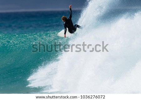 Surfer rear unidentified photo surfing action speed top turn on fast ocean wave.