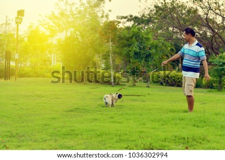 Happy Asian man playing with his dog in garden #1036302994
