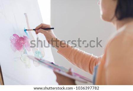 art, creativity and people concept - close up of artist with palette and brush painting still life on paper at studio #1036397782