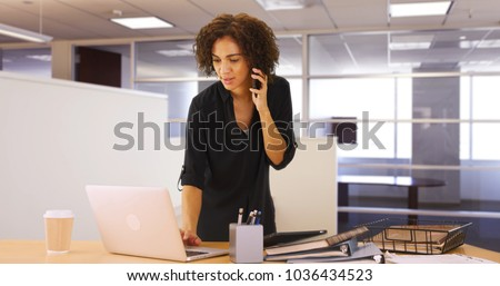 Businesswoman using laptop computer in office while listening on smartphone device #1036434523