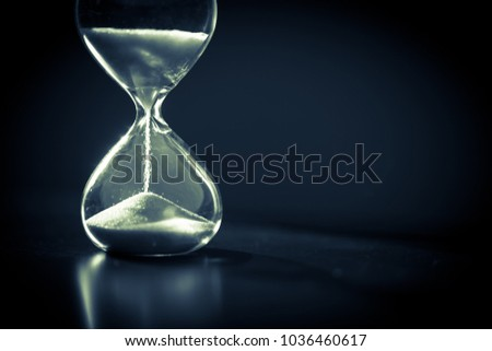 Hourglass as time passing concept for business deadline, urgency and running out of time. Sandglass, egg timer on dark background showing the last second or last minute or time out.  With copy space. #1036460617