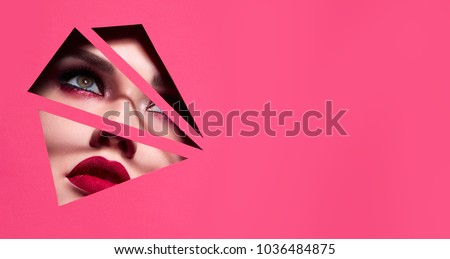 the face of a young beautiful girl with a bright make-up and with plump red lips peeks into a hole in pink paper.Fashion, beauty, make-up, cosmetics, beauty salon, style, personal care, geometry. #1036484875