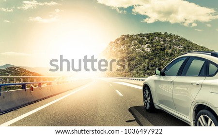 White car rushing along a high-speed highway. Toned photo. #1036497922