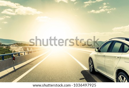 White car rushing along a high-speed highway. Toned photo. #1036497925