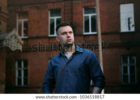 beautiful guy on the street in the shirt near the building #1036518817