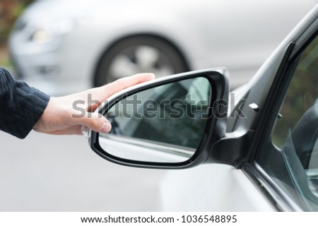 Young human hand is preparing or correct car mirror for the trip or travel from car window. #1036548895