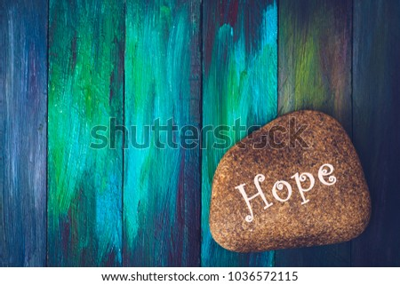 """words  """"Hope"""" painted on river stone over colorful wooden background, vignette and vintage tone with copy space for your text"""
