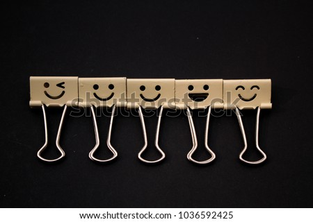 five different types of smiling  face paper clip isolated with black background.